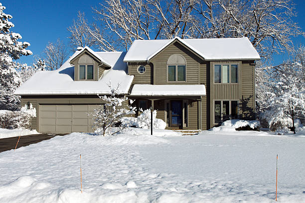 Suburban colonial house in winter snow Color DSLR stock picture of green and grey suburban colonial style house covered in bright, white winter snow.  Clear, cold background for home is bright blue sky.  Black top driveway is clear, but lawn is blanketed.  No people in shot but ample copy space for text colonial style stock pictures, royalty-free photos & images