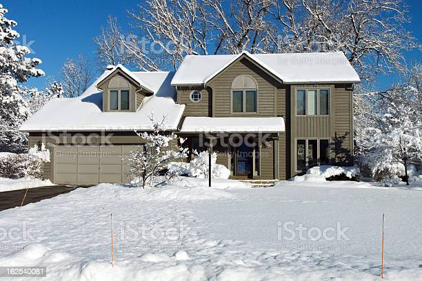 Photo of Suburban colonial house in winter snow