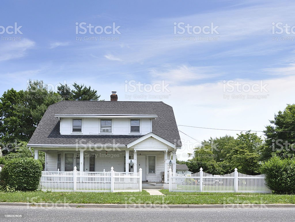 Suburban Cottage Home with White Picket Fence stock photo
