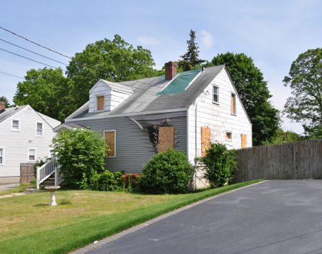 Suburban Cape Cod style Home Fire Damage Boarded Windows USA