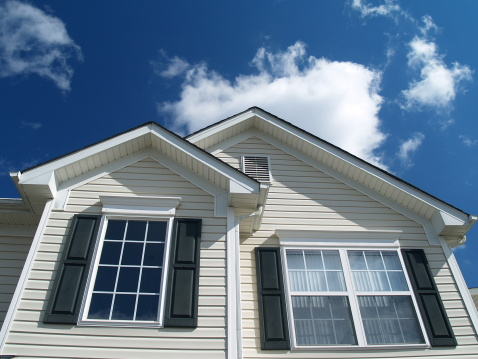 Closeup of Suburban Home with bright blue sky and white clouds