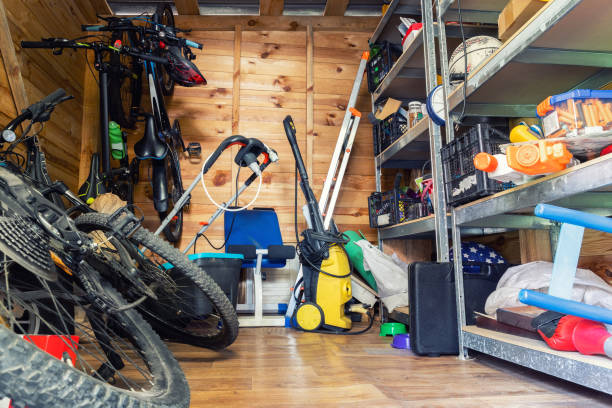 Suburban home wooden storage utility unit shed with miscellaneous stuff on shelves, bikes, exercise machine, ladder, garden tools and equipment.