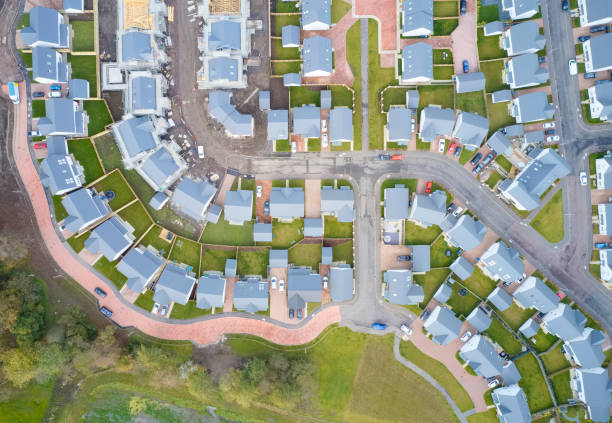 Suburban houses in row aerial view in summer illuminating gardens Suburban houses in row aerial view in summer illuminating gardens uk housing development stock pictures, royalty-free photos & images