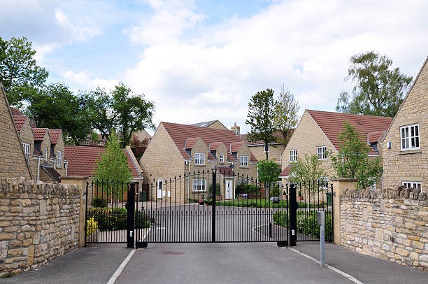 Suburban Houses Entrance and Driveway of a Suburban Housing Estate gated community stock pictures, royalty-free photos & images