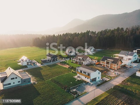 Family homes in the country side in winter time, by the forest. Aerial view, drone point of view, flying over a new housing development. Situated in the country side in Slovenia. Forming a small new neighborhood. Modern architecture had a an influence on design of these new family homes.