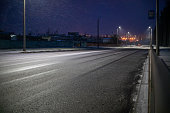 istock Suburban road with lights on a winter snow evening 1214137253