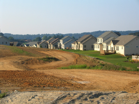New development being made. Shows backs of houses and dirt area where a road or more houses will go.