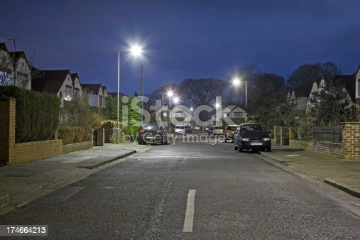A modern street scene with small townhouses lit by street lamps.Please see the following lightboxes for more