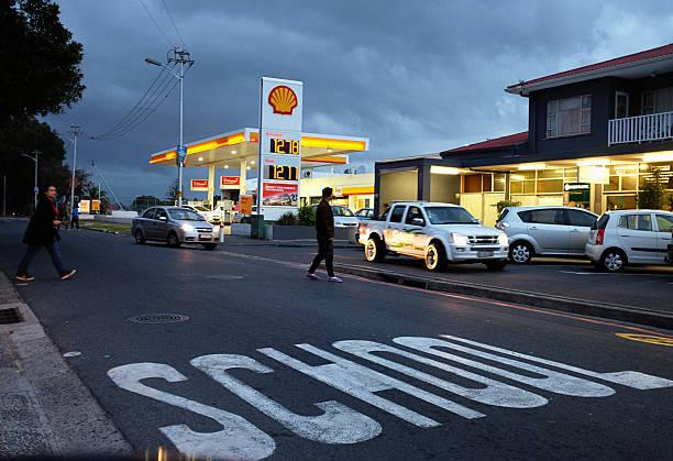 suburban strip mall at sunset with shell gas statkion - walking home sunset street bildbanksfoton och bilder