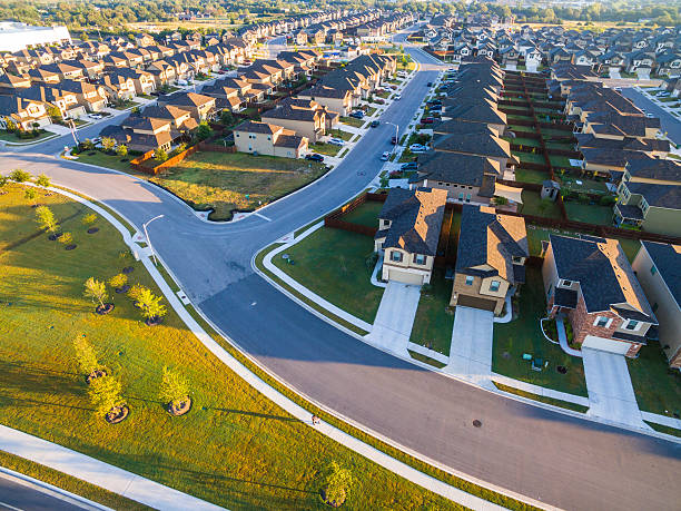 Suburbia Community Aerial Over Austin Round Rock Texas Suburbia Community Aerial Over Austin Round Rock Texas with curved street and new development completed with new trees and green grass field looking down from Above neighborhood  cookie cutter stock pictures, royalty-free photos & images
