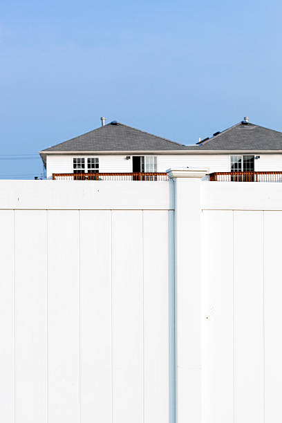 Suburbia - White fence and houses behind it stock photo