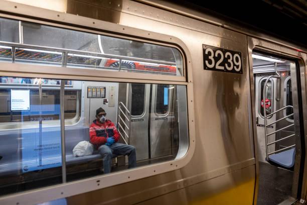 Subway commuter wearing respirator mask in New York City stock photo
