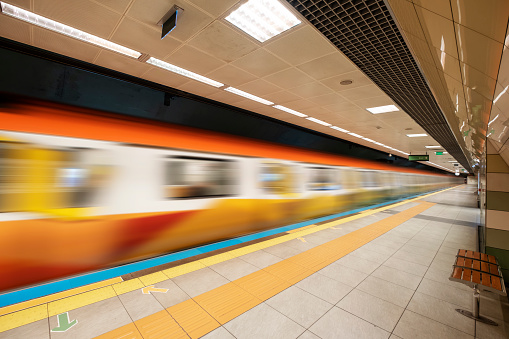 Wide angle shot of subway leaving, no people at the station. Motion blurred effect on subway. Horizontal composition with copy space.