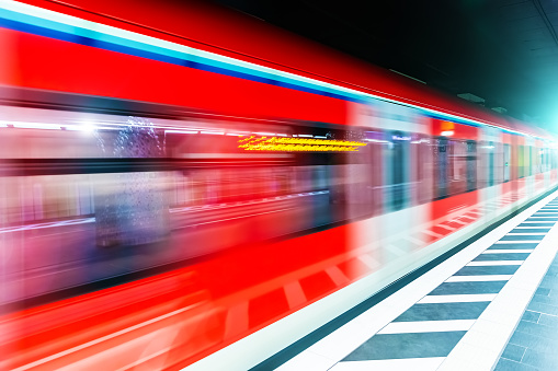 Creative abstract commuter city business travel transportation concept: subway underground metro train at railway station platform with high speed motion blur effect