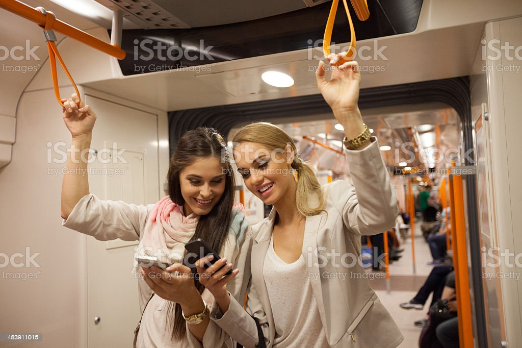 Subway passengers with smart phones Focus on two women taking a subway and using smart phones. 20-24 Years Stock Photo
