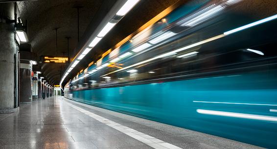 Subway station platform and departing train - long exposure