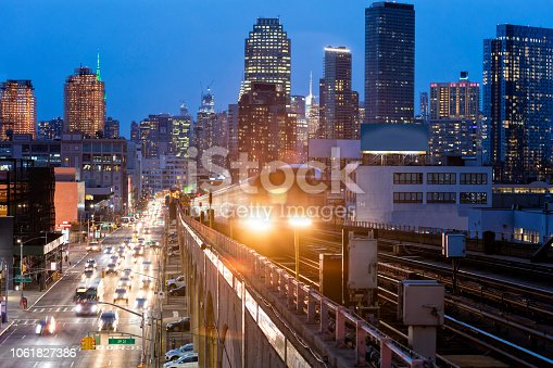 Train approaching  elevated subway station in Queens at dusk, New York. Financial buildings and New York skyline are seen in the background, on the left below can be seen a busy street full of cars at rush hour, USA.