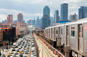 Train approaching  elevated subway station in Queens, New York. Financial buildings and New York skyline are seen in the background, on the left below can be seen a busy street full of cars at rush hour, USA.