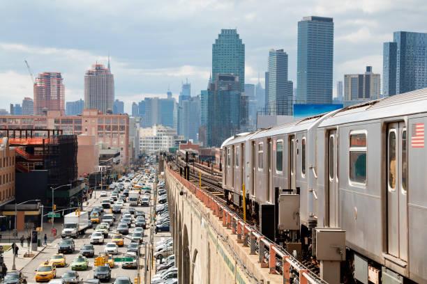 U-Bahn-Zug nähert sich Erhöhter U-Bahn-Station in Queens, New York – Foto