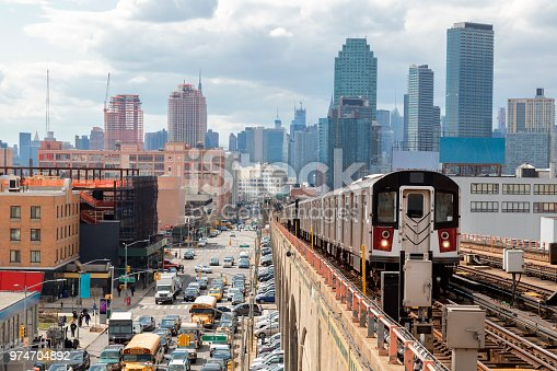 Train approaching  elevated subway station in Queens, New York. Financial buildings and New York skyline are seen in the background, on the left below can be seen a busy street full of cars at rush hour, cloudy, dramatic sky, USA.