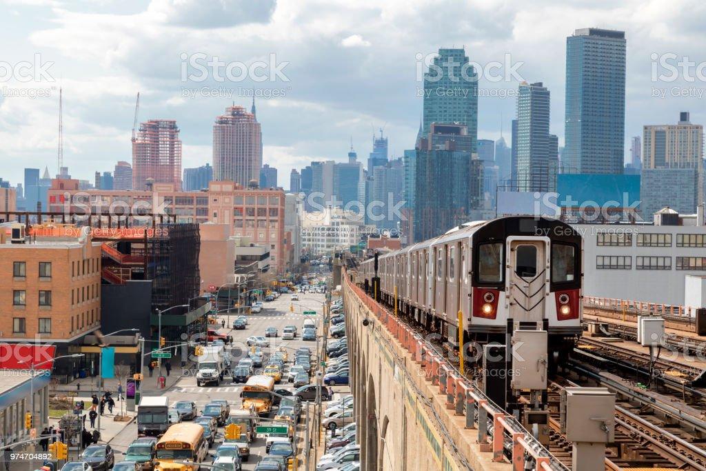 U-Bahnzug nähern erhöhten U-Bahn-Station in Queens, New York  – Foto