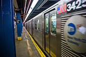 In New York City, United States a subway train passes in a motion blur as it departs from the 103 Street Manhattan station platform.