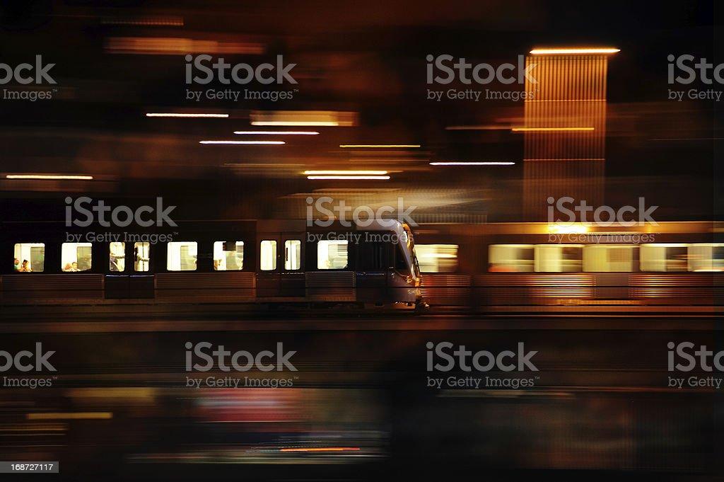 Subway train in profile crossing bridge by night royalty-free stock photo