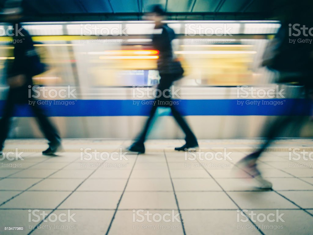 Subway train leaving station. People on platform. stock photo
