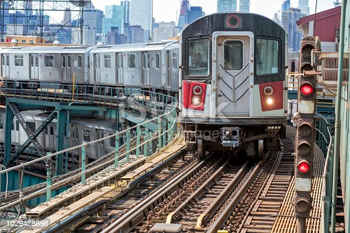 Train approaching  elevated subway station in Queens, New York. Financial buildings and New York skyline are seen in the background, two subway trains speeding one above the other, USA.