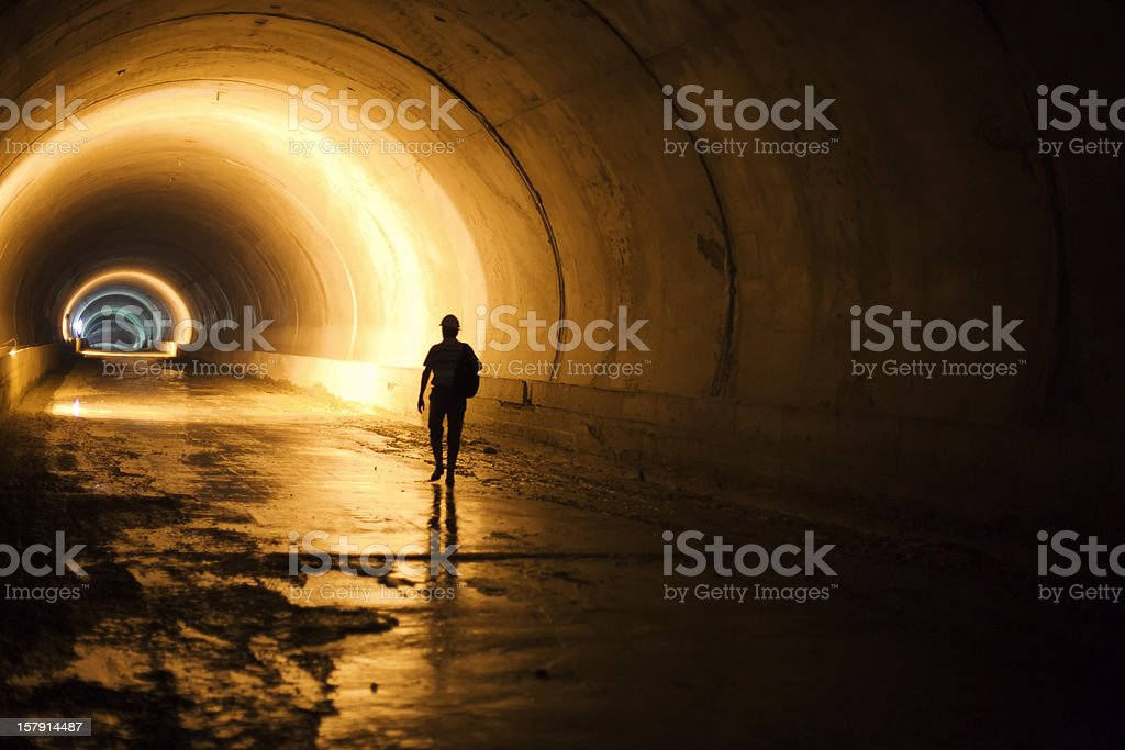 Subway tunnel construction with silhouette of walking worker stock photo
