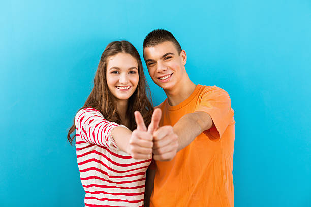Succesfull students showing thumbs up Teenage boy and teenage girl (age 15) showing thumbs-up to the camera, standing in front of the blue wall. Focus is on teenagers. cute teen couple stock pictures, royalty-free photos & images