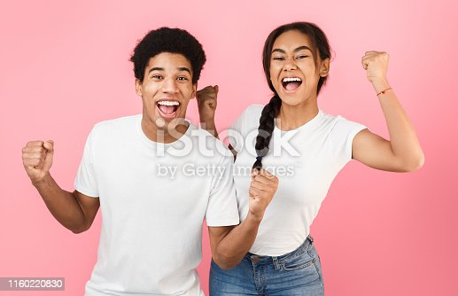 istock Success. African-american teens raising their hands happily 1160220830