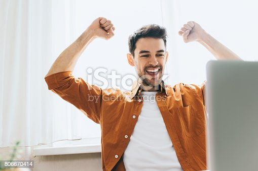 istock Success and achievement concept. Headshot of businessman, looking at the laptop with happy cheerful smile achieving life goals. Happy Caucasian male student sitting in office make winner gesture. 806670414