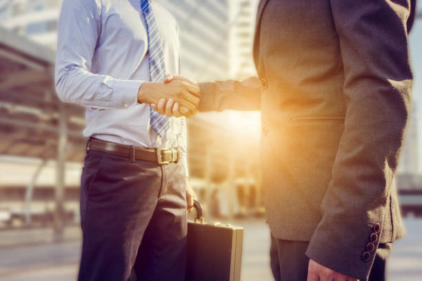 success and happiness concept, businessman handshake at city outside office. - sales stock pictures, royalty-free photos & images
