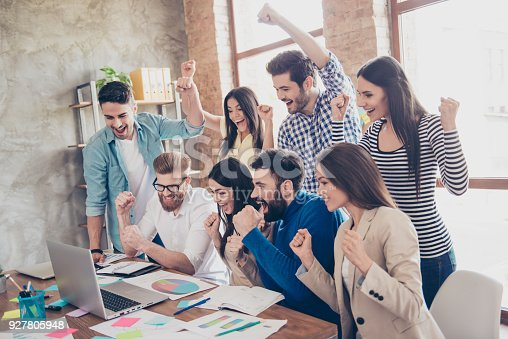 istock Success and team work concept. Group of business partners with raised up hands in light modern workstation, celebrating the breakthrough in their company 927805948