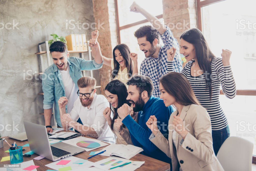 Success and team work concept. Group of business partners with raised up hands in light modern workstation, celebrating the breakthrough in their company stock photo