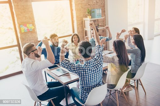 istock Success and team work concept. Team of business partners with raised up hands in light modern workstation, celebrating the breakthrough in their company 939732326