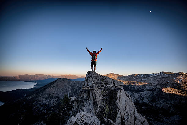 Success and Victory in the mountains A climber reaches the summit of an exposed mountain top in the Tahoe backcountry, California achievement stock pictures, royalty-free photos & images