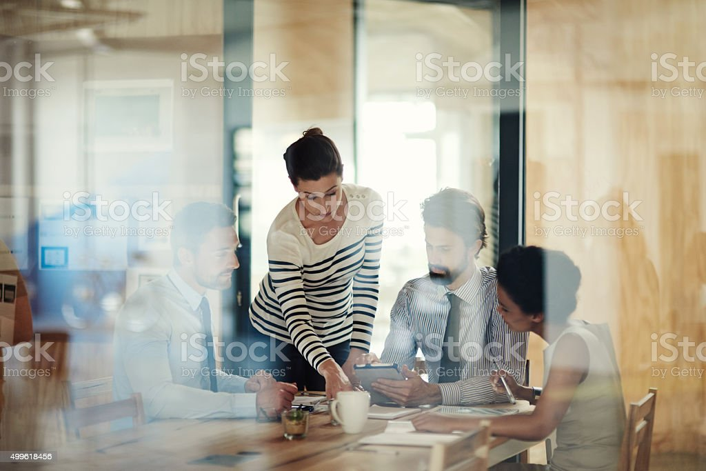 Through the glass shot of a group of colleagues working together in...