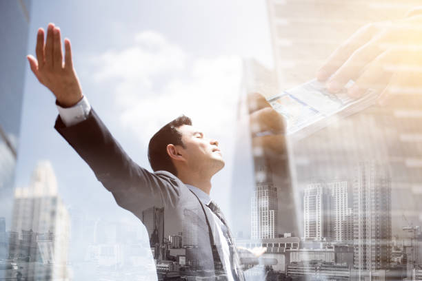 Success businessman in the city raising his arms, open palms, with face looking up stock photo