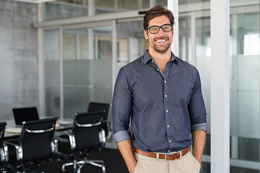 Portrait of young businessman wearing eyeglasses and standing outside conference room. Portrait of happy business man wearing spectacles and looking at camera with copy space. Satisfied proud man feeling confident in a modern office.