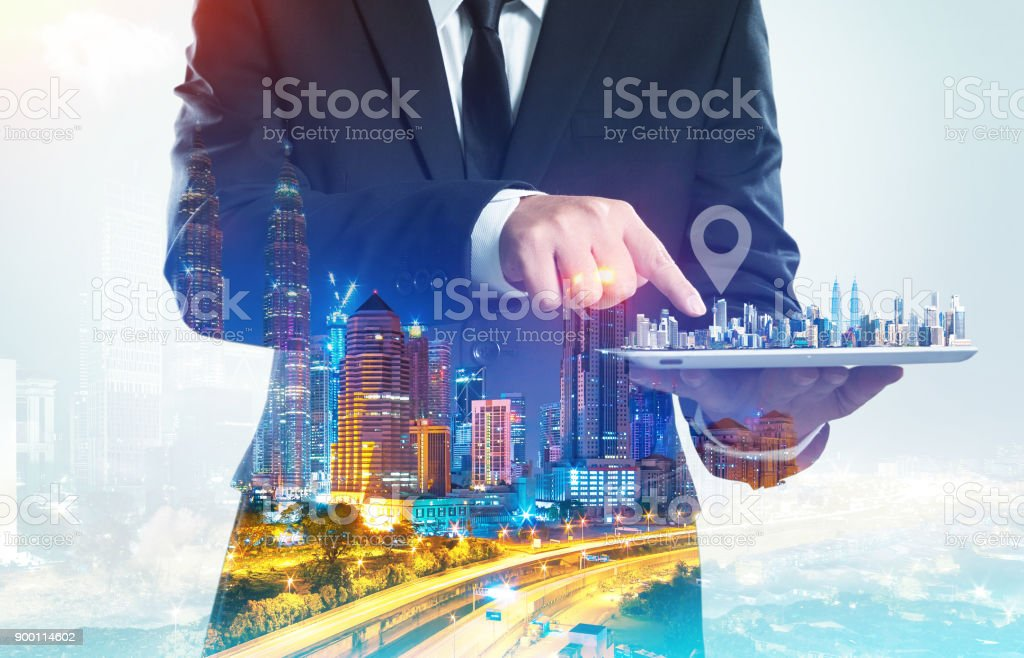 Success businessman using digital tablet show the home on virtual screen with night cityscape double exposure effect  . stock photo