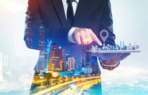 homme d'affaires de succès à l'aide de tablette numérique montrent la maison sur un écran virtuel avec effet de double exposition nuit paysage urbain. - business malaysia photos et images de collection