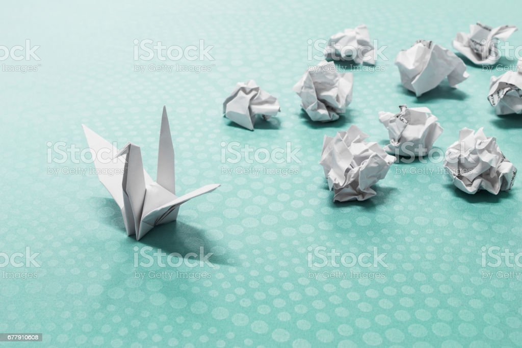 Success concept, A origami paper bird and crumpled paper balls stock photo