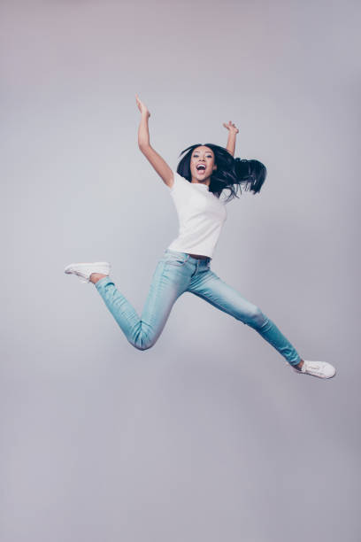 success, dream, femenine girlish life concept. chill relaxing mode. excited mixed race brunette lady model is jumping up, wearing casual clothes, white shoes, on pure light grey background, - african youth jumping for joy stock photos and pictures