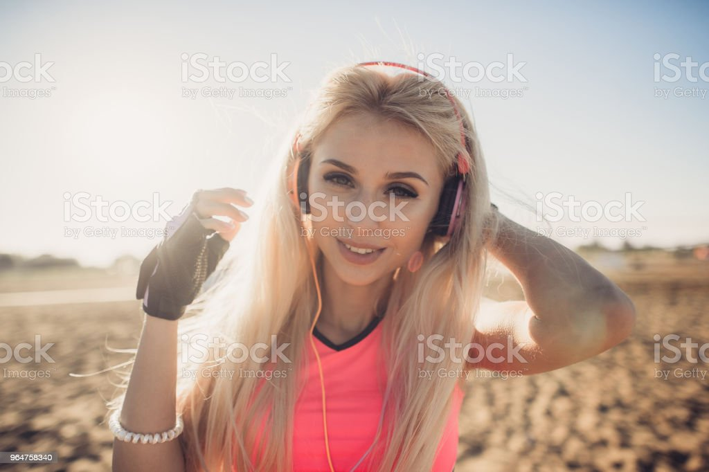 Success fitness woman concept with sports armband and earphones. Winning concept of female athlete runner cheering with arms raised up for achievement in weight loss or life goal royalty-free stock photo