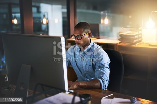 Cropped shot of a handsome young businessman using a computer during a late night in a modern office