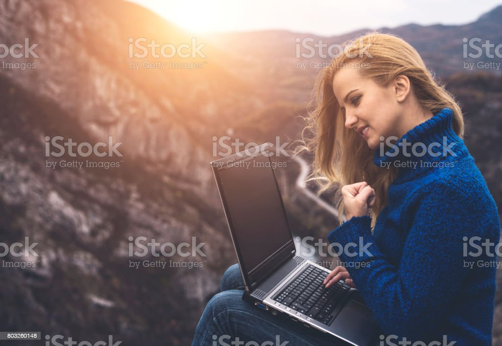 Success. Girl using laptop in nature stock photo