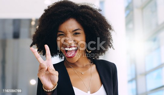 Portrait of a confident young businesswoman showing a peace gesture in a modern office
