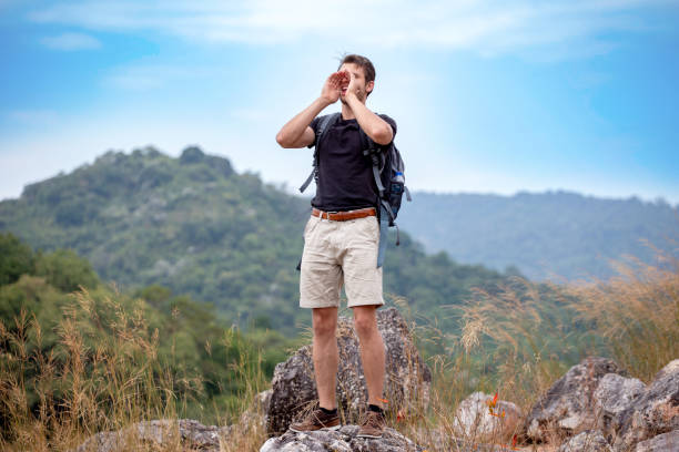 Success Hiker man shouting with hands cupped around mouth on the top mountain after hiking to goal  . achievement adventure. stock photo